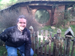 Keith Turner standing by a Hobbit Hole on the Hobbiton Set.